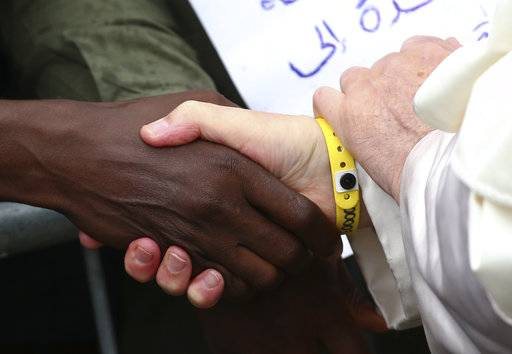 Pope Francis, right, wears an identification bracelet as he meets with migrants at a regional migrant center, in Bologna, Italy, Sunday, Oct. 1, 2017. Pope Francis is in Cesena and Bologna for a one-day visit. (Alessandro Bianchi/ Pool photo via AP)