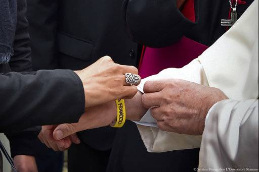 Pope Francis, right, wears an identification bracelet as he meets with migrants at a regional migrant center, in Bologna, Italy, Sunday, Oct. 1, 2017. Pope Francis is in Cesena and Bologna for a one-day visit. (L'Osservatore Romano/ Pool photo via AP)