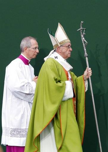 Pope Francis leads Monsignor Guido Marini, the papal master of liturgical ceremonies, as he celebrates Mass at the Renato Dall'Ara stadium in Bologna, Italy, Sunday, Oct. 1, 2017. Pope Francis is on a one-day visit to the northern Italian towns of Cesena and Bologna.