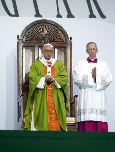 Pope Francis is flanked by Monsignor Guido Marini, the papal master of liturgical ceremonies, as he celebrates Mass at the Renato Dall'Ara stadium in Bologna, Italy, Sunday, Oct. 1, 2017. Pope Francis is on a one-day visit to the northern Italian towns of Cesena and Bologna.