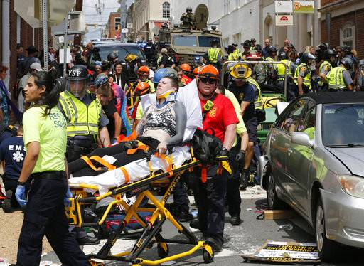FILE - In this Aug. 12, 2017 file photo, rescue personnel help injured people who were hit when a car ran into a large group of protesters after a white nationalist rally in Charlottesville, Va. Attacks this summer on counter-protesters in Charlottesville, Virginia, and an empty Air Force recruiting station in Oklahoma had the hallmarks of terrorist attacks. But they weren't prosecuted as such.