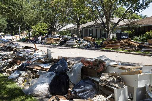 FILE - In this Sept. 7, 2017 file photo, flood damaged debris from homes lines the street in the aftermath of Hurricane Harvey in Houston. One month after Harvey dumped record rainfall in the Houston area, many neighborhoods and suburbs of the nation's fourth largest city continue cleaning up after the storm. While the larger shelters have closed and much of the city has gone back to normal, huge piles of debris still line streets in numerous neighborhoods as many residents try to salvage their homes.