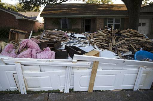 FILE - In this Sept. 6, 2017, file photo, debris sits in front of a home in the aftermath of Hurricane Harvey in Houston. One month after Harvey dumped record rainfall in the Houston area, many neighborhoods and suburbs of the nation's fourth largest city continue cleaning up after the storm. While the larger shelters have closed and much of the city has gone back to normal, huge piles of debris still line streets in numerous neighborhoods as many residents try to salvage their homes.