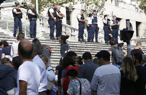 Passengers wait in front a line a police officers blocking the access to Marseille 's main train station Sunday, Oct. 1, 2017 in Marseille, southern France. French police have warned people to avoid Marseille's main train station following a knife attack that made at least one dead.
