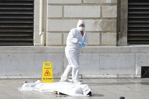 Investigative police officers works by a body under a white sheet outside Marseille 's main train station Sunday, Oct. 1, 2017 in Marseille, southern France. A man with a knife attacked people at the main train station in the southeastern French city of Marseille on Sunday, killing two women before soldiers fatally shot the assailant, officials said.