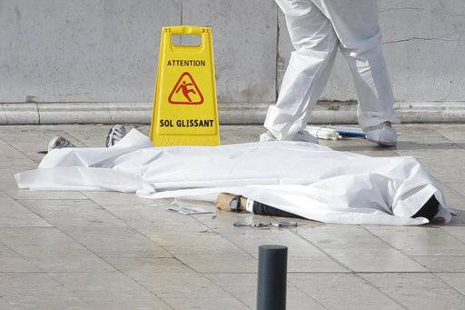 An investigative police officer works by a body under a white sheet outside Marseille 's main train station Sunday, Oct. 1, 2017 in Marseille, southern France. A man with a knife attacked people at the main train station in the southeastern French city of Marseille on Sunday, killing two women before soldiers fatally shot the assailant, officials said.