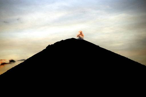 Mount Agung volcano is seen at sunset in Karangasem, Bali, Indonesia, Sunday, Oct. 1, 2017. A week after authorities put Bali's volcano on high alert, tremors that indicate an eruption is coming show no sign of abating and continues to swell the exodus from the region.