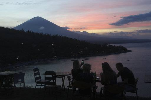 Tourists watch the sunset over the Mount Agung volcano in Karangasem, Bali, Indonesia, Sunday, Oct. 1, 2017.  A week after authorities put Bali's volcano on high alert, tremors that indicate an eruption is coming show no sign of abating, swelling the exodus from the region to at least 140,000 people.