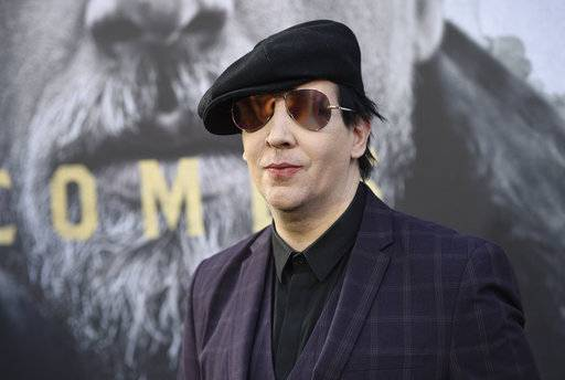 "FILE - In his May, 8, 2017, file photo, Marilyn Manson arrives at the world premiere of ""King Arthur: Legend of the Sword"" at the TCL Chinese Theatre in Los Angeles. Marilyn Manson's representative said Saturday, Sept. 30, 2017, that the singer was injured in a mishap on stage during a New York City performance and taken to a hospital. (Chris Pizzello/Invision via AP, File)"