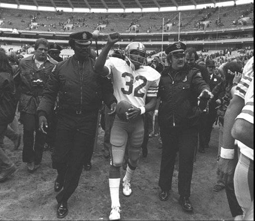 FILE - In this Dec. 16, 1979 file photo, San Francisco 49ers running back O.J. Simpson is escorted from the field by police after the final NFL football game of his career against in the Atlanta Falcons at Atlanta Fulton County Stadium in Atlanta, Ga. Simpson retired from football after the 1979 season, later being inducted into the Pro Football Hall of Fame and beginning careers in acting and football broadcasting. A Nevada prison official said early Sunday, Oct. 1, 2017, O.J. Simpson, the former football legend and Hollywood star, has been released from a Nevada prison in Lovelock after serving nine years for armed robbery.