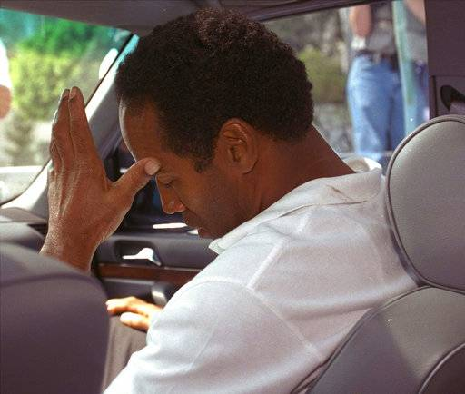 FILE - In this June 13, 1994, file photo, former pro running back O.J. Simpson hangs his head as he sits in his attorney's car after being questioned by Los Angeles Police into the death of his ex-wife, Nicole Brown Simpson. The bodies of the 35-year-old woman and an unidentified 26-year-old man, apparent stabbing victims, were discovered after midnight Sunday in her Los Angeles area home.