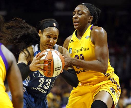 Minnesota Lynx forward Maya Moore, left, drives to the basket against Los Angeles Sparks forward Nneka Ogwumike during the first half in Game 4 of the WNBA basketball finals, Sunday, Oct. 1, 2017, in Los Angeles.