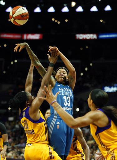 Minnesota Lynx guard Seimone Augustus, center, passes the ball over Los Angeles Sparks forward Nneka Ogwumike (30) and forward Candace Parker, right, during the first half in Game 4 of the WNBA basketball finals, Sunday, Oct. 1, 2017, in Los Angeles.