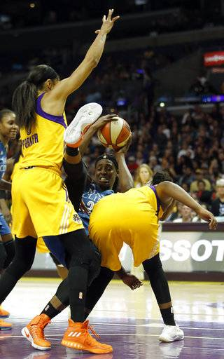 Minnesota Lynx center Sylvia Fowles, center, falls to the floor holding onto the ball with Los Angeles Sparks forward Candace Parker, left, defending with guard Chelsea Gray during the first half in Game 4 of the WNBA basketball finals, Sunday, Oct. 1, 2017, in Los Angeles.