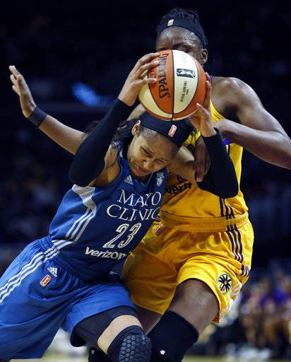 Minnesota Lynx forward Maya Moore, left, drives to the basket and picks up a foul on Los Angeles Sparks forward Nneka Ogwumike during the first half in Game 4 of the WNBA basketball finals, Sunday, Oct. 1, 2017, in Los Angeles.
