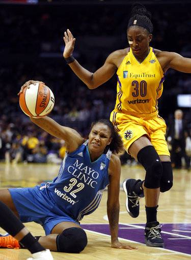 Minnesota Lynx forward Rebekkah Brunson, left, keeps her dribble, but falls to the floor against Los Angeles Sparks forward Nneka Ogwumike during the first half in Game 4 of the WNBA basketball finals, Sunday, Oct. 1, 2017, in Los Angeles.