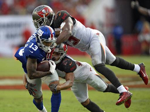 New York Giants wide receiver Odell Beckham (13) is stopped by Tampa Bay Buccaneers cornerback Brent Grimes (24) and outside linebacker Adarius Glanton after a reception during the fourth quarter of an NFL football game Sunday, Oct. 1, 2017, in Tampa, Fla.