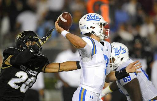 UCLA quarterback Josh Rosen, center, passes as Colorado linebacker Drew Lewis, left, reaches in during the first half of an NCAA college football game, Saturday, Sept. 30, 2017, in Pasadena, Calif.