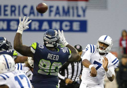 Indianapolis Colts quarterback Jacoby Brissett (7) passes under pressure from Seattle Seahawks defensive tackle Jarran Reed (90), in the first half of an NFL football game, Sunday, Oct. 1, 2017, in Seattle.