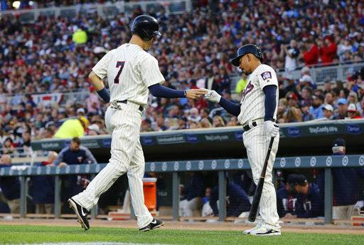 Minnesota Twins' Joe Mauer, left, is greeted by Eduardo Escobar after Mauer scored on a bases loaded walk by Detroit Tigers pitcher Buck Farmer during the first inning of a baseball game Saturday, Sept. 30, 2017, in Minneapolis.