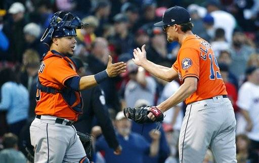 Houston Astros' Tyler Clippard (19) and Juan Centeno celebrate after defeating the Boston Red Sox 4-3 during a baseball game in Boston, Sunday, Oct. 1, 2017.