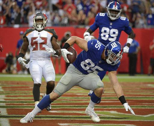 New York Giants tight end Rhett Ellison (85) scores on a 2-yard touchdown reception in front of Tampa Bay Buccaneers linebacker Cameron Lynch (52) and Giants' Jerell Adams (89) during the fourth quarter of an NFL football game Sunday, Oct. 1, 2017, in Tampa, Fla.