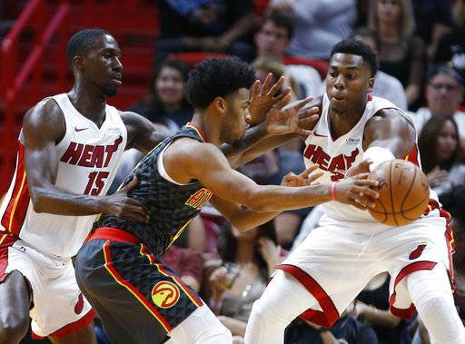 Atlanta Hawks guard Quinn Cook, center, attempts to pass past Miami Heat forward Okaro White (15) and center Hassan Whiteside during the first half of an NBA preseason basketball game, Sunday, Oct. 1, 2017, in Miami.