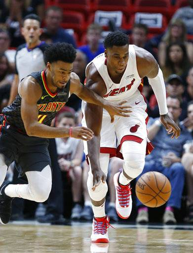Atlanta Hawks guard Quinn Cook, left, and Miami Heat center Hassan Whiteside chase down the ball during the first half of an NBA preseason basketball game, Sunday, Oct. 1, 2017, in Miami.