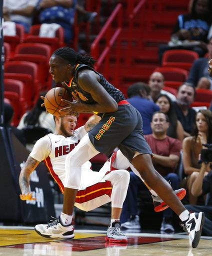 Atlanta Hawks forward Taurean Prince, right, fouls Miami Heat guard Tyler Johnson as he goes up for a shot during the first half of an NBA preseason basketball game, Sunday, Oct. 1, 2017, in Miami.