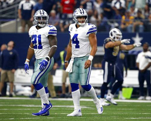 Dallas Cowboys running back Ezekiel Elliott (21) and quarterback Dak Prescott (4) walk off the field after an unsuccessful two-point conversion attempt on a pass to wide receiver Terrance Williams in the second half of an NFL football game against the Los Angeles Rams on Sunday, Oct. 1, 2017, in Arlington, Texas.