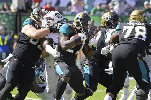 Jacksonville Jaguars' Leonard Fournette, center, runs the ball during the first half of an NFL football game against the New York Jets, Sunday, Oct. 1, 2017, in East Rutherford, N.J.