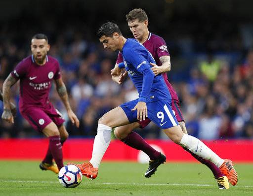 Chelsea's Alvaro Morata, left, is challenged for the ball by Manchester City's John Stones during their English Premier League soccer match between Chelsea and Manchester City at Stamford Bridge stadium in London, Saturday, Sept. 30, 2017.