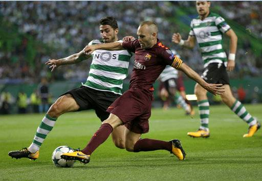 Barcelona's Andres Iniesta, right, challenges for the ball with Sporting's Cristiano Piccini during a Champions League, Group D soccer match between Sporting CP and FC Barcelona at the Alvalade stadium in Lisbon, Wednesday Sept. 27, 2017.