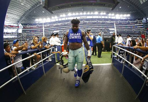 Dallas Cowboys running back Ezekiel Elliott (21) walks off the field holding the jersey of Los Angeles Rams running back Todd Gurley after their NFL football game, Sunday, Oct. 1, 2017, in Arlington, Texas.