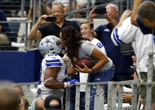 Dallas Cowboys' Ezekiel Elliott hands the football and gets a kiss from his mother Dawn, right, in the end zone after scoring against the Los Angeles Rams in the first half of an NFL football game, Sunday, Oct. 1, 2017, in Arlington, Texas.