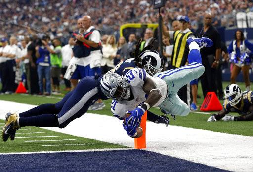 Dallas Cowboys running back Ezekiel Elliott (21) gets past Los Angeles Rams linebacker Mark Barron (26) to score a touchdown on a carry in the first half of an NFL football game, Sunday, Oct. 1, 2017, in Arlington, Texas.