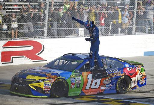 Kyle Busch celebrates atop his car after he won the NASCAR Cup Series auto race, Sunday, Oct. 1, 2017, at Dover International Speedway in Dover, Del.
