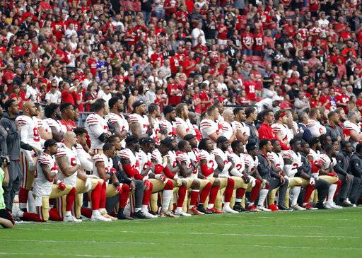 Members of the San Francisco 49ers kneel during the national anthem as others stand during the first half of an NFL football game against the Arizona Cardinals, Sunday, Oct. 1, 2017, in Glendale, Ariz.