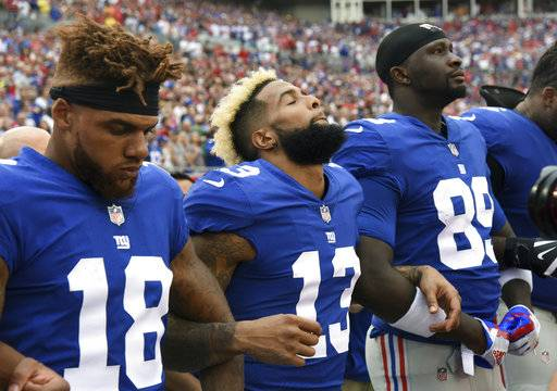 New York Giants, from left, Roger Lewis (18), Odell Beckham (13), and Jerell Adams (89) lock arms during the playing of the National Anthem before an NFL football game against the Tampa Bay Buccaneers Sunday, Oct. 1, 2017, in Tampa, Fla.