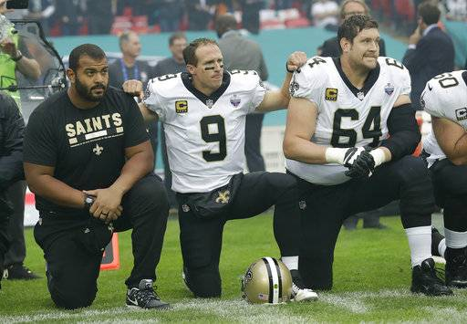 New Orleans Saints quarterback Drew Brees (9) kneels down with teammates before the U.S. national anthem was played ahead of an NFL football game against the Miami Dolphins at Wembley Stadium in London, Sunday Oct. 1, 2017. Saints players then stood when the anthem was played.