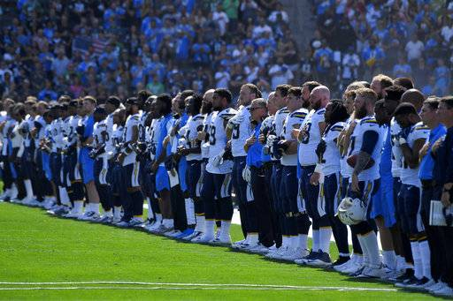 The Los Angeles Chargers lock arms during the playing of the national anthem before an NFL football game against the Philadelphia Eagles, Sunday, Oct. 1, 2017, in Carson, Calif.