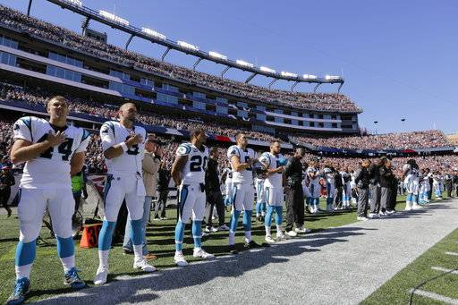 Members of the Carolina Panthers stand along the sideline during the national anthem before an NFL football game against the New England Patriots, Sunday, Oct. 1, 2017, in Foxborough, Mass.