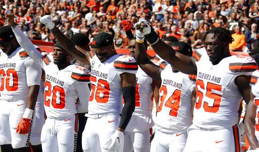 Cleveland Browns teammates raise their fists during the national anthem before an NFL football game against the Cincinnati Bengals, Sunday, Oct. 1, 2017, in Cleveland.