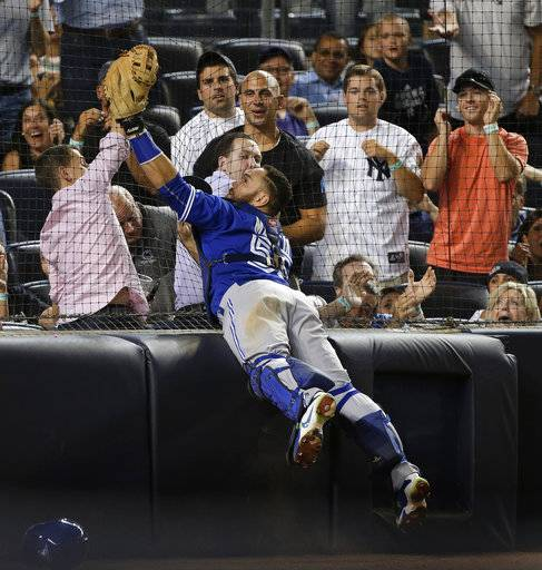 FILE - In this Friday, Aug. 7, 2015 file photo, Toronto Blue Jays catcher Russell Martin (55) catches a pop foul by New York Yankees' Stephen Drew as he leaps against the backstop netting during the seventh inning of a baseball game at Yankee Stadium in New York. The New York Yankees plan to expand protective netting at their home ballpark and spring training complex next year. The team announced the decision during its final regular-season game Sunday, Oct. 1, 2017 against Toronto.