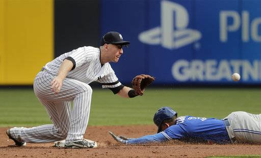 Toronto Blue Jays' Ezequiel Carrera steals second base safely ahead of the tag from New York Yankees third baseman Todd Frazier during the fifth inning of a baseball game, Friday, Sept. 29, 2017 in New York.