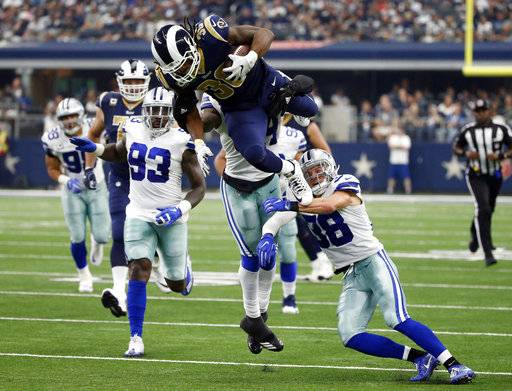 Los Angeles Rams running back Todd Gurley (30) is stopped by Dallas Cowboys linebacker Jaylon Smith, rear, and safety Jeff Heath (38) after Gurley lept over Heath on a carry in the second half of an NFL football game, Sunday, Oct. 1, 2017, in Arlington, Texas.