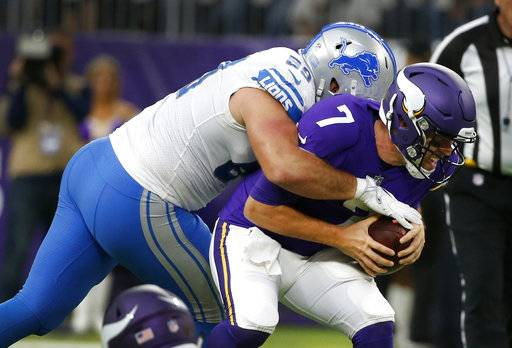 Minnesota Vikings quarterback Case Keenum (7) is sacked by Detroit Lions defensive end Anthony Zettel, left, during the first half of an NFL football game, Sunday, Oct. 1, 2017, in Minneapolis.