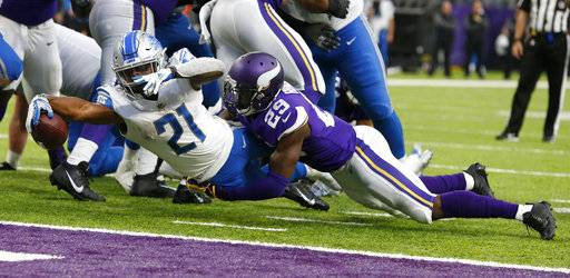 Detroit Lions running back Ameer Abdullah (21) scores on a 3-yard touchdown run ahead of Minnesota Vikings cornerback Xavier Rhodes (29) during the second half of an NFL football game, Sunday, Oct. 1, 2017, in Minneapolis.