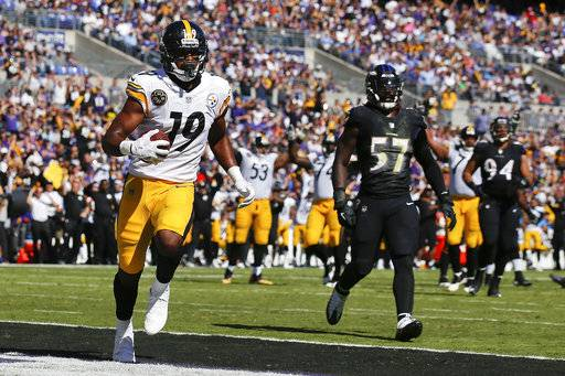 Pittsburgh Steelers wide receiver JuJu Smith-Schuster (19) carries the ball into the end zone for a touchdown as Baltimore Ravens inside linebacker C.J. Mosley (57) watches during the first half of an NFL football game in Baltimore, Sunday, Oct. 1, 2017.
