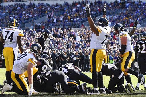 Pittsburgh Steelers offensive guard Ramon Foster (73) celebrates running back Le'Veon Bell's (26) touchdown during the first half of an NFL football game against the Baltimore Ravens in Baltimore, Sunday, Oct. 1, 2017.